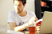 man sits by laptop with cup of coffee