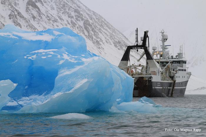 Bilde av forskningskipet Helmer Hansen ved siden av et isfjell
