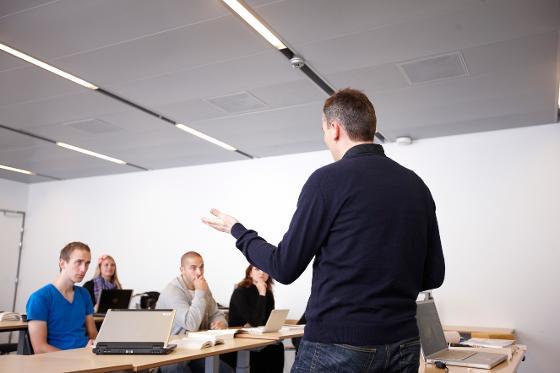 Mann står foran klasse og underviser