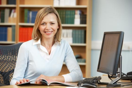 Kvinne sitter ved pult med datamaskin og smiler mot kamera