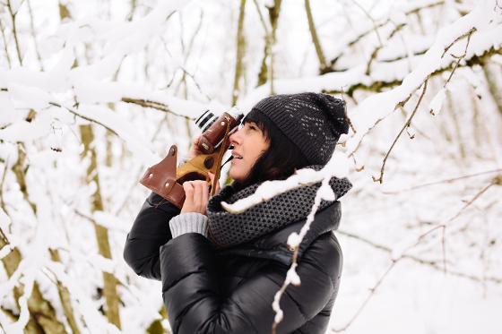 Ung dame tar bilder med et retro-kamera ute en nedsnedd vinterskog.