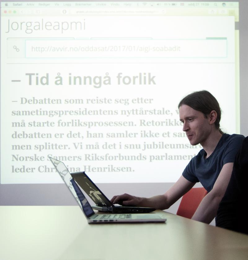 Nå kan flere følge med i debattene i samiske medier. På veggen bak Kevin Unhammer er en maskinoversatt versjon av en artikkel i den samiske avisa Ávvir.