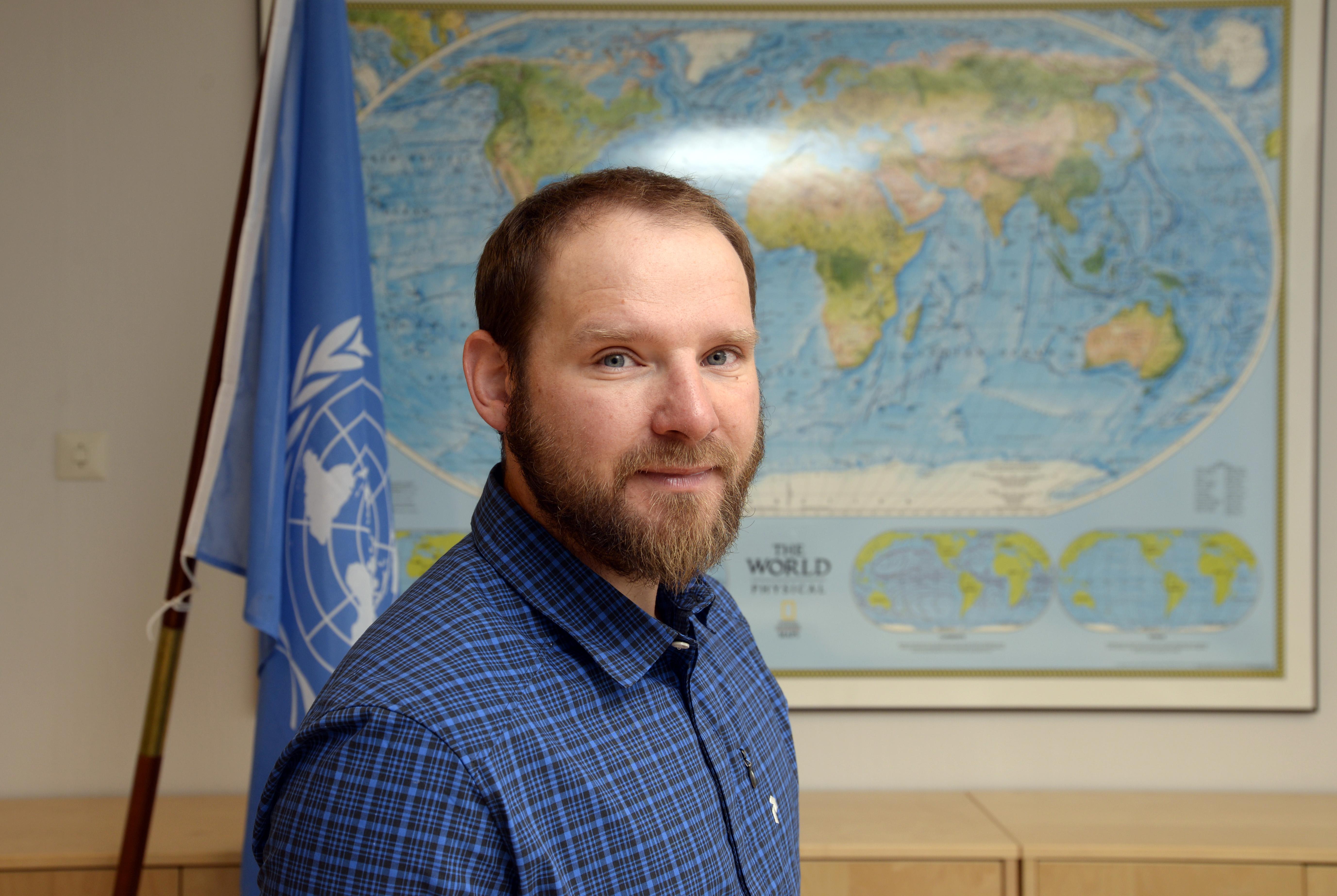 Tim Dassler foran FN-flagget og verdenskartet