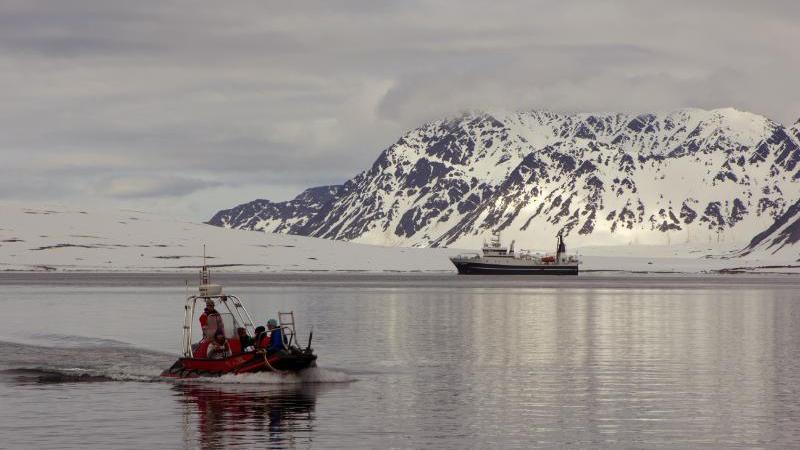Lettbåt og forskningsskip i en fjord foran fjell. Foto: Jørn Berger-Nyvoll