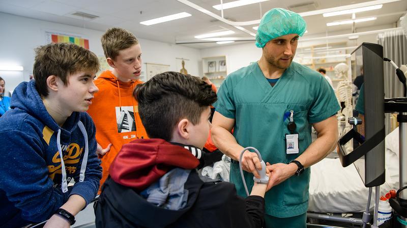 Morten N. Sivertsen som underviser i sykepleie demonstrerer medisinsk utstyr for tre elever fra videregående. Foto: Lars Åke Andersen