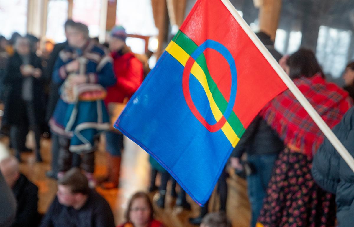 Det samiske flagget og festpyntede personer innendørs.