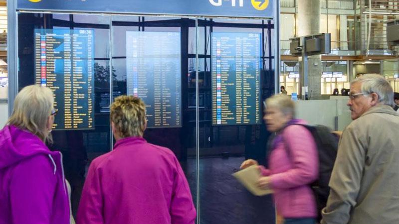Personer på foran skilt på flyplass. Foto: Mostphotos