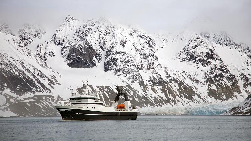 """UiTs forskningsfartøy """"Helmer Hanssen"""" i Magdalenefjorden på Svalbard. Foto: Karine Nigar Aarskog/UiT"""