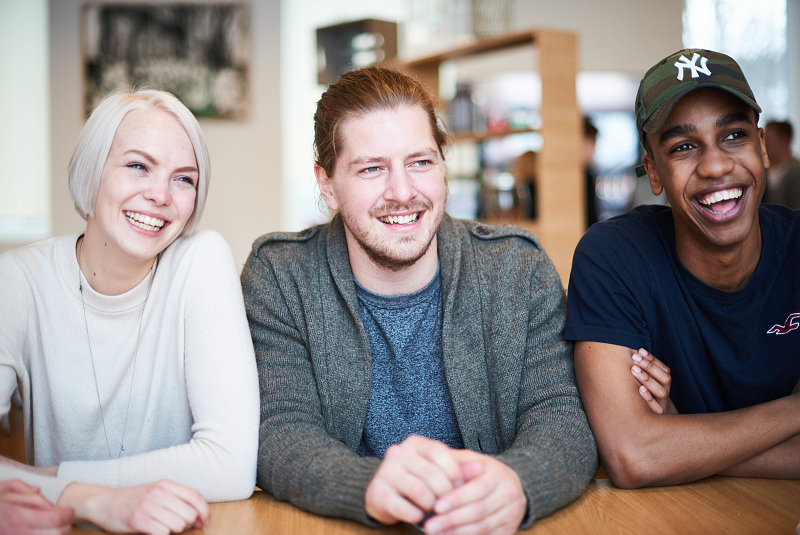 3 studenter sitter rundt et bord