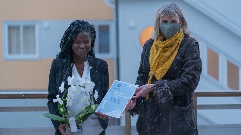 2 damer står utendørs, hvor ene mottar et diplom fra den andre