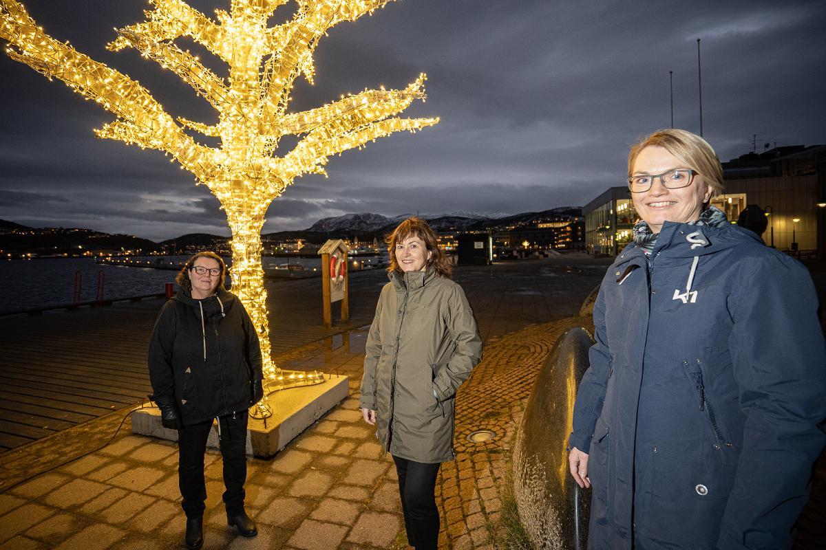 3 damer står utendørs foran et julebelyst tre