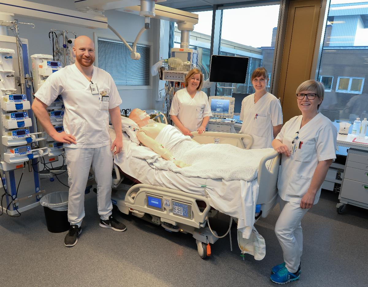 FIre intensivsykepleiere rundt en sykeseng på UNN, TRomsø.