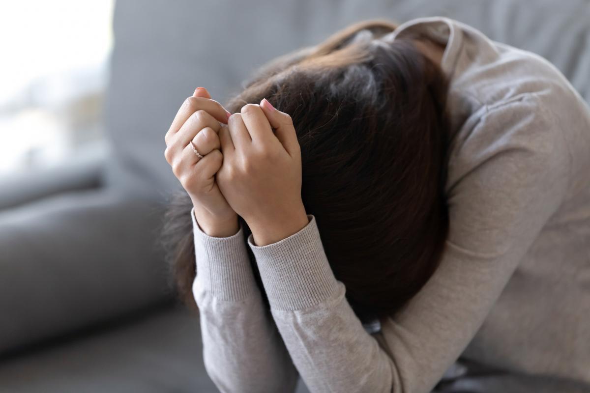 Trist ung kvinne lener seg framover med armene bøyd over hodet