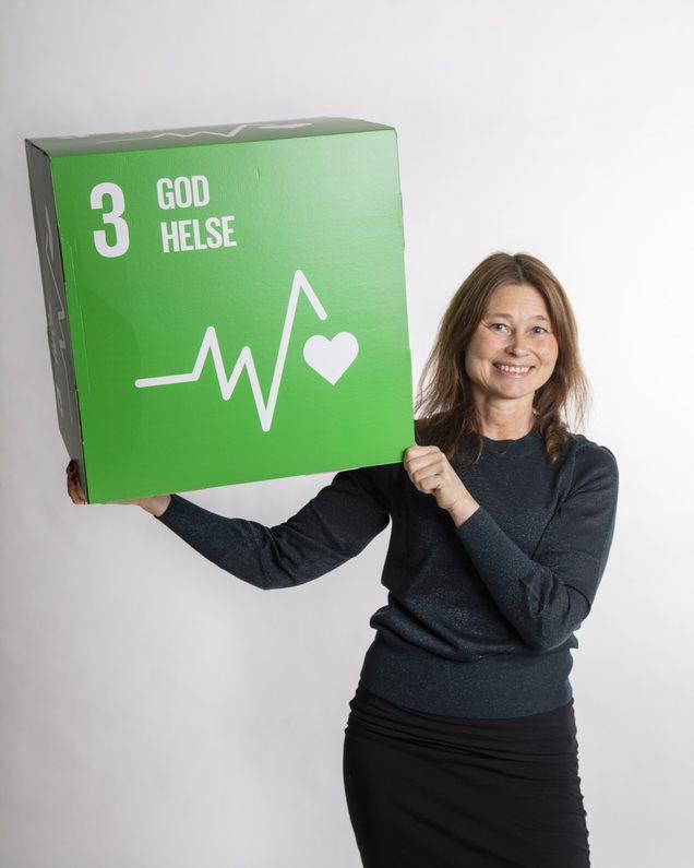 Kristin B. Borch smiler og holder opp en stor grønn boks med FNs bærekraftsmål