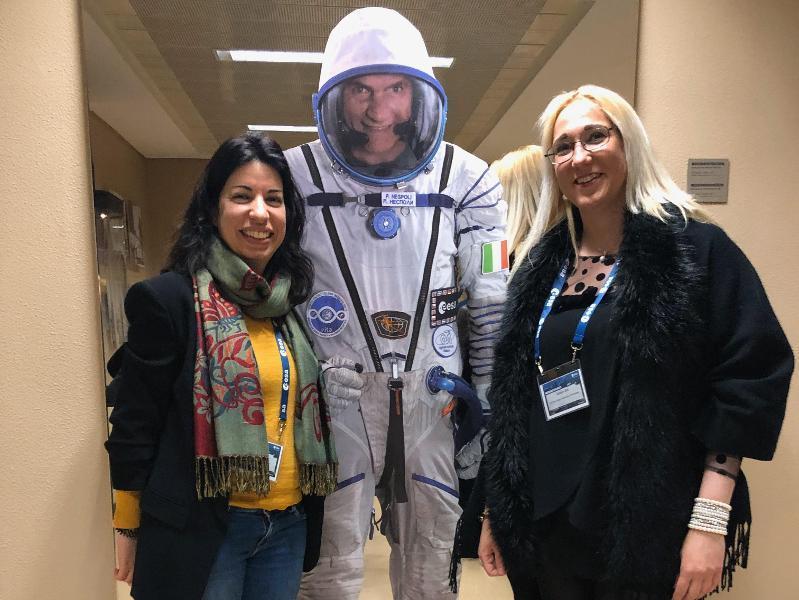Tre mennesker står ved siden av hverandre, en med romutstyr.