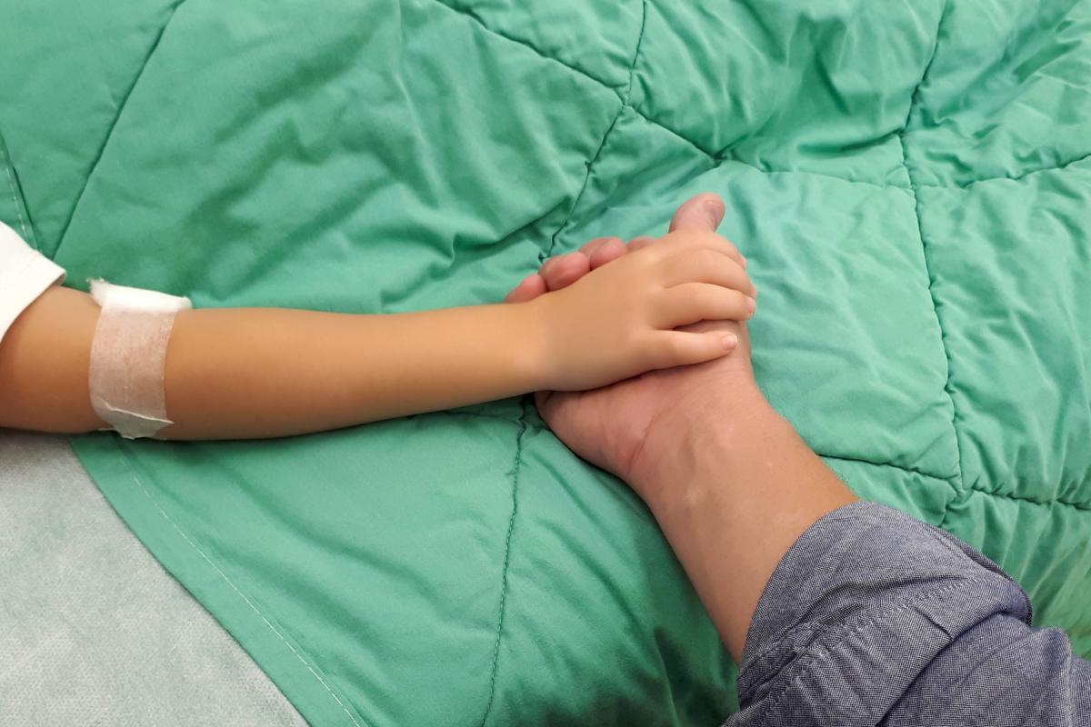 Barnehånd som holder en voksenhånd på et sykehus.