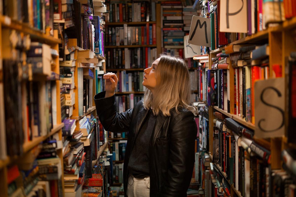 Student leter etter bøker i bibliotekreoler