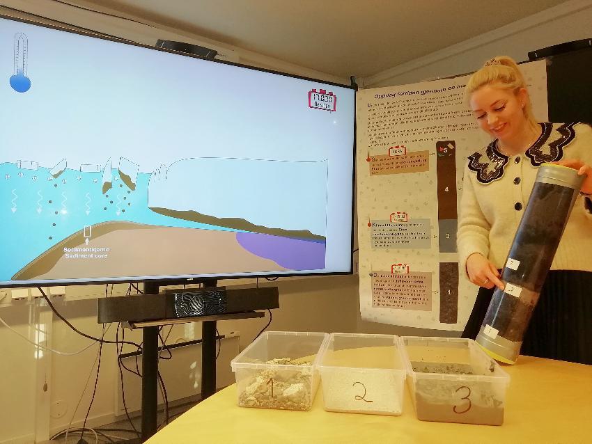 Stine Bjordal Olsen forklarer innholdet i sedimentkjernen hentet fra kontinentalskråningen utenfor Tromsø. Den viser forskjellige lag avsatt under forskjellig påvirkning av isen som dekket Nord-Europa under siste istid.
