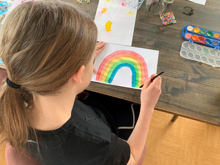jente som maler regnbue i forbindelse med koronanedstenging