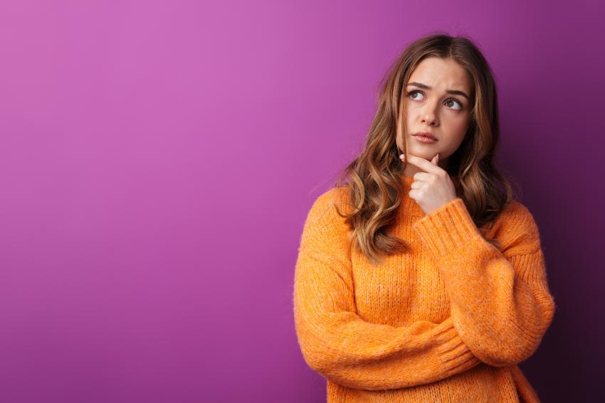 Ung jente i oransje genser, ser tenksom og tvilende ut