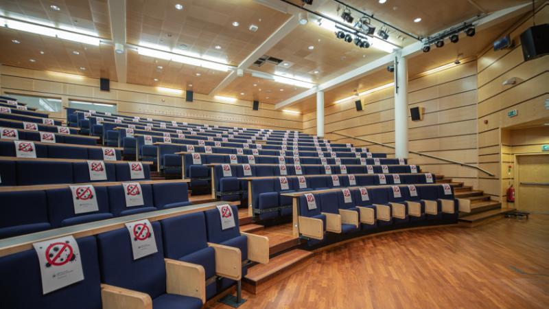 Et auditorium som er tomt, stolene er merket med smittevernplakater.