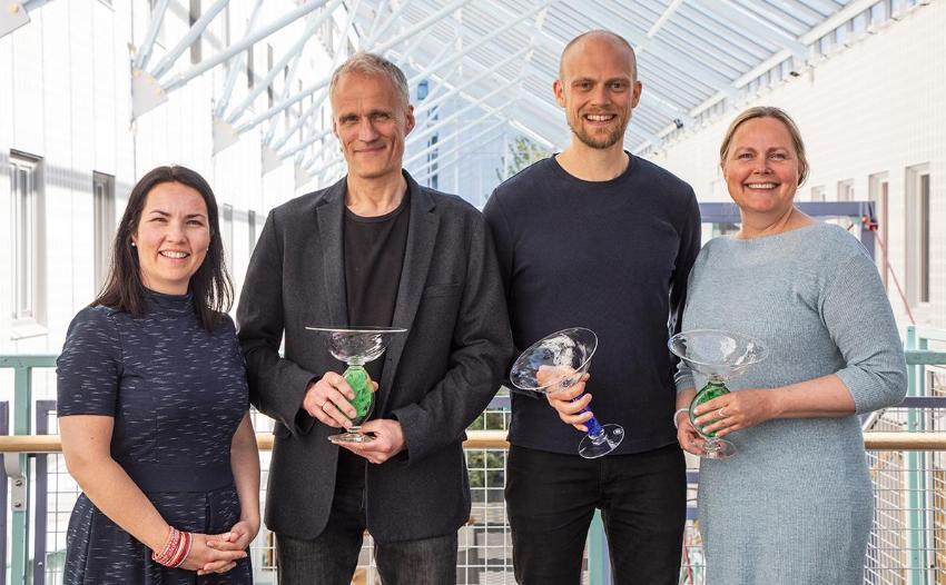 Fire smilende menn og kvinner med hvert sitt trofé i hånden.