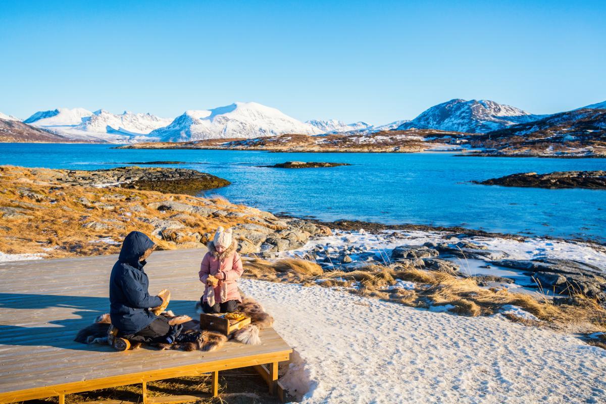 piknik på nordnorsk strand med snø og sol.