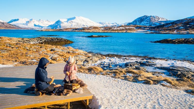 To personer i vinterlandskap i Nord-Norge med hav og fjell. Foto: Mostphotos