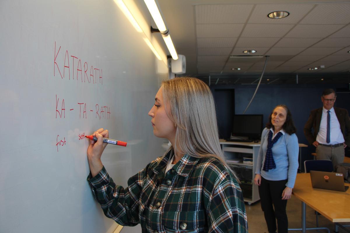 Ung kvinne, Marte Isaksen, skriver på tavla med entusiastiske lærere i bakgrunnen (professor Laura Janda og Tore Nesset)