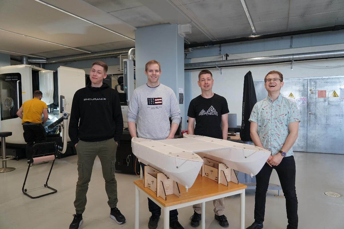 Fire studenter samlet rundt en mindre modell av en katamaran brukt som autonomt fartøy.