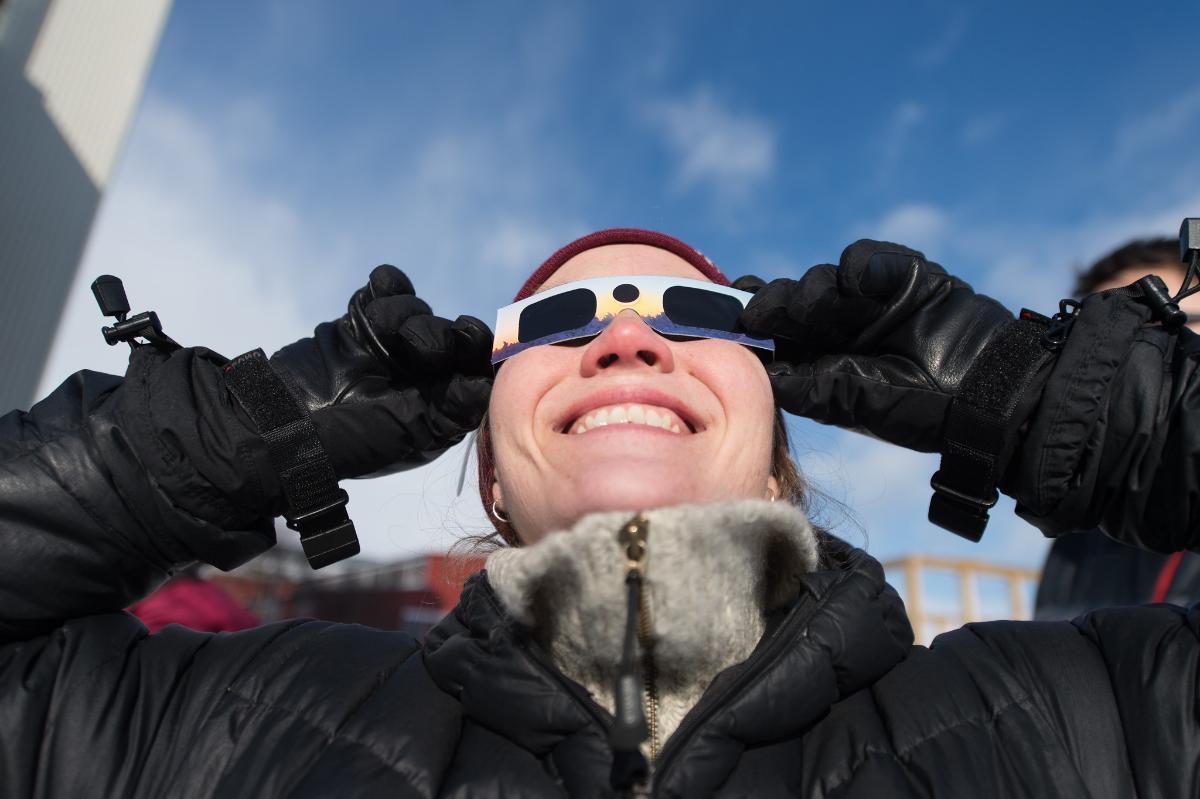 Kvinne med solformørkelsesbriller