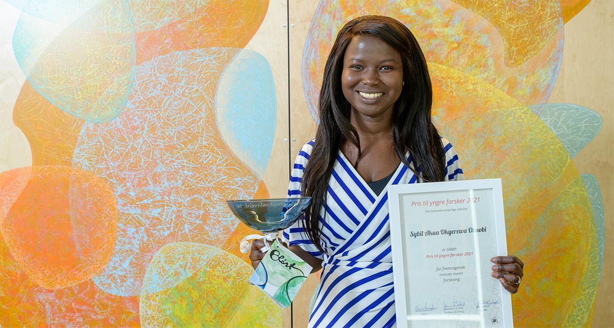 Bilde av en smilende dame i stripete kjole som holder et trofé i glass og et innrammet diplom.