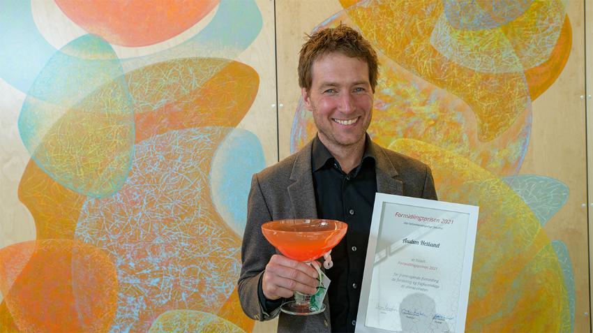 Smilende mann som holder et innrammet diplom og et glasstrofé.