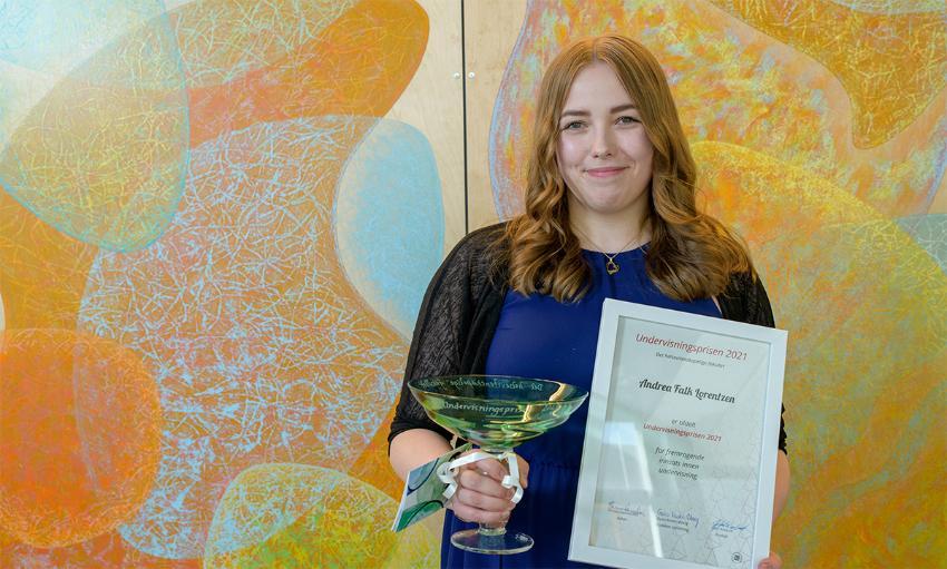Smilende dame med langt, brunt, hår som står smilende og holder et trofé i glass og et innrammet diplom.