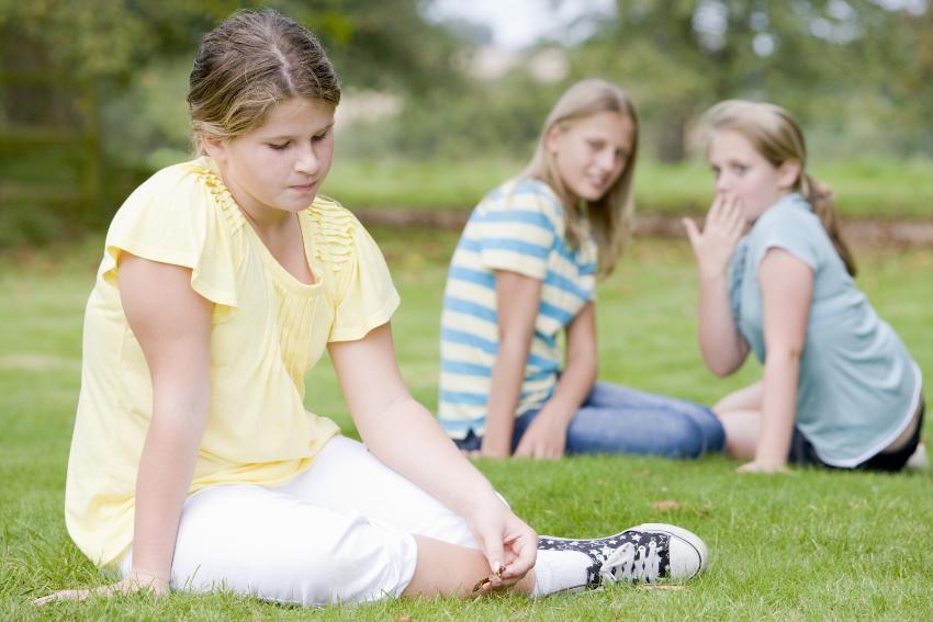 To jenter utestenger en tredje jente, ute på en gressplen. De hvisker og ser på den tredje jenta.