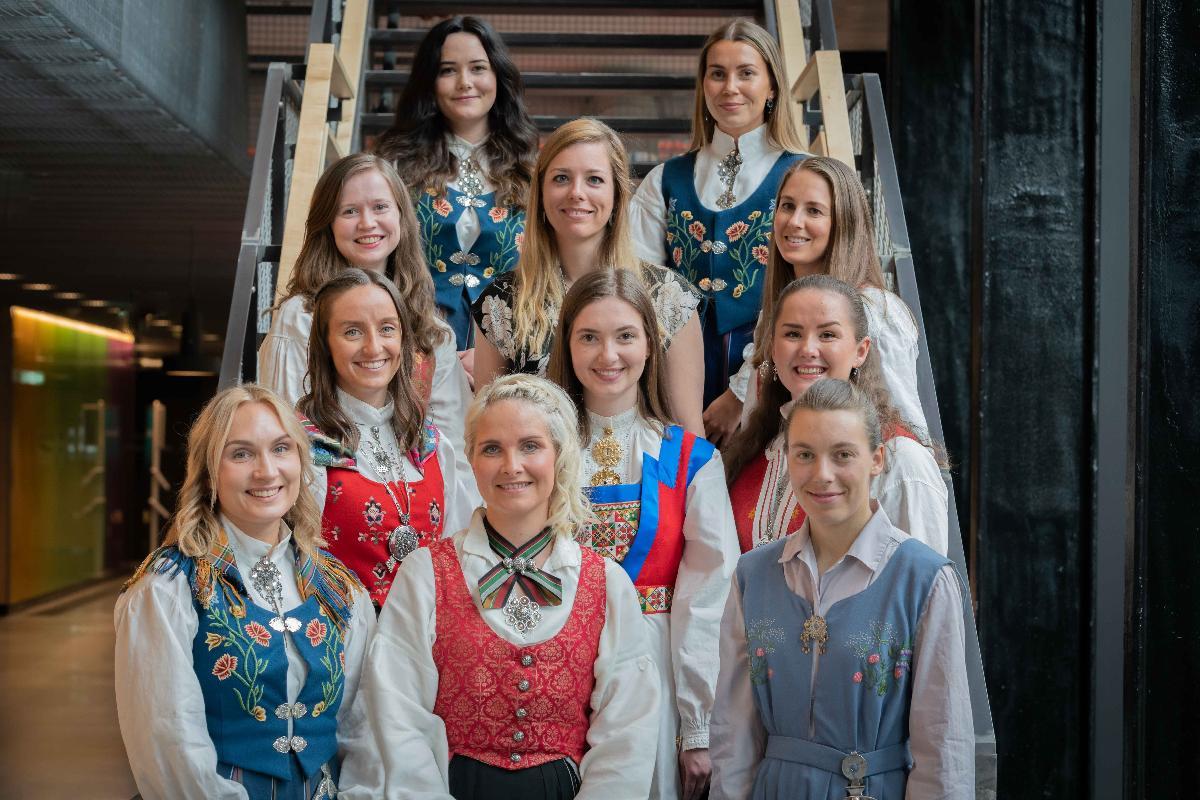 Gruppebilde av 11 jenter med ulike bunader som står oppstilt i en trapp