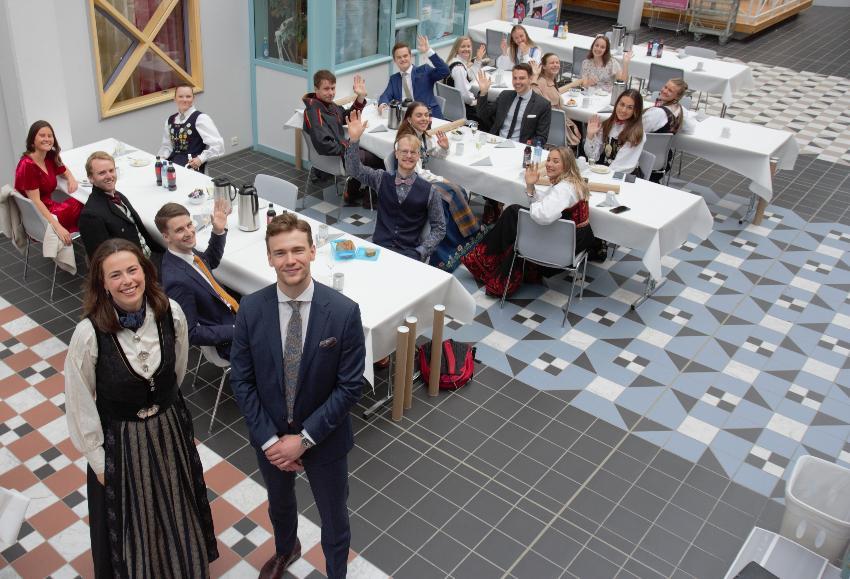 To unge mennesker, Camilla Wahlstrøm og Fredrik Alfhei er i ført bunad og dress og smiler til kamera med medstudentene i bakgrunnen.