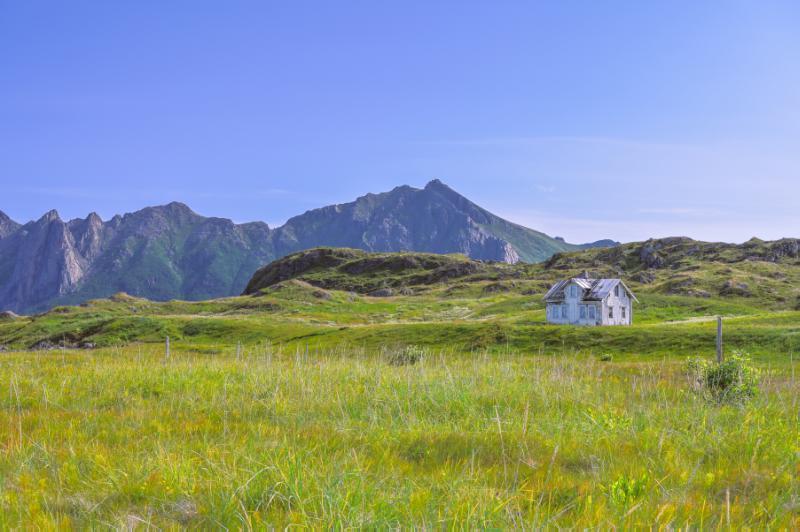 Landskap i Vesterålen.  Forlatt hus og høye fjell.