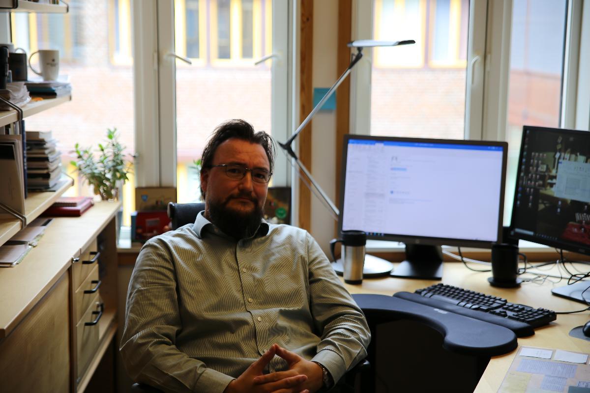 Bilde av Magne Frostad tatt i profil. Frostad sitter på kontoret sitt og ser rett inn i kameraet.