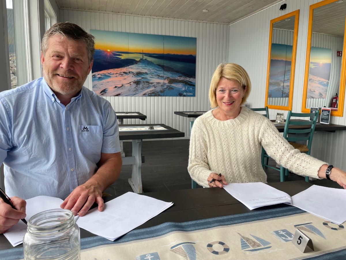 To personer som sitter i en sofa og signerer en avtale
