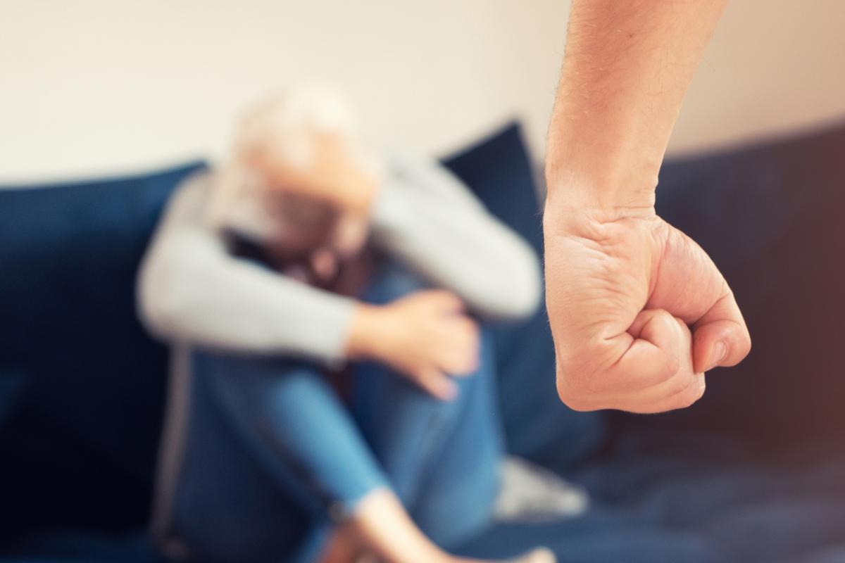 Knyttet håndneve og kvinne i sofa