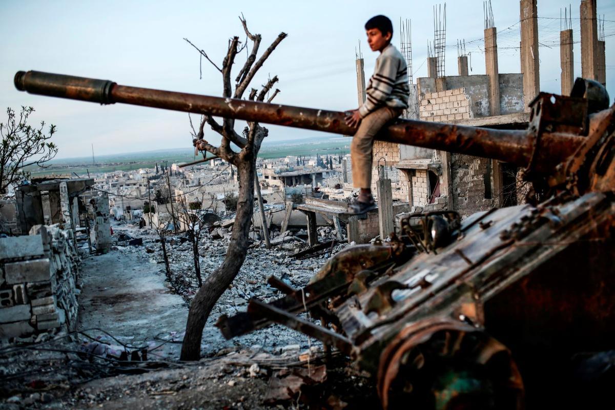gutt i syria sitter oppå tanks i ruiner