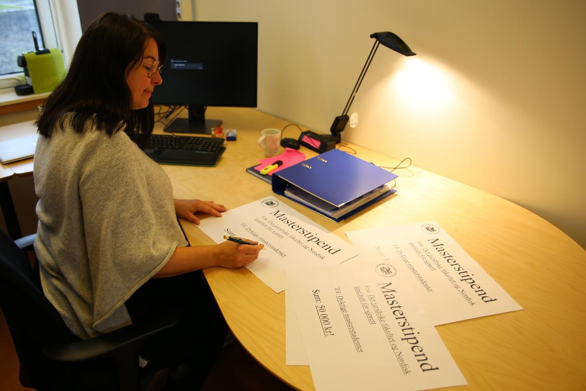 Irene Dahl ser på ark som skal illustrere masterstipender.