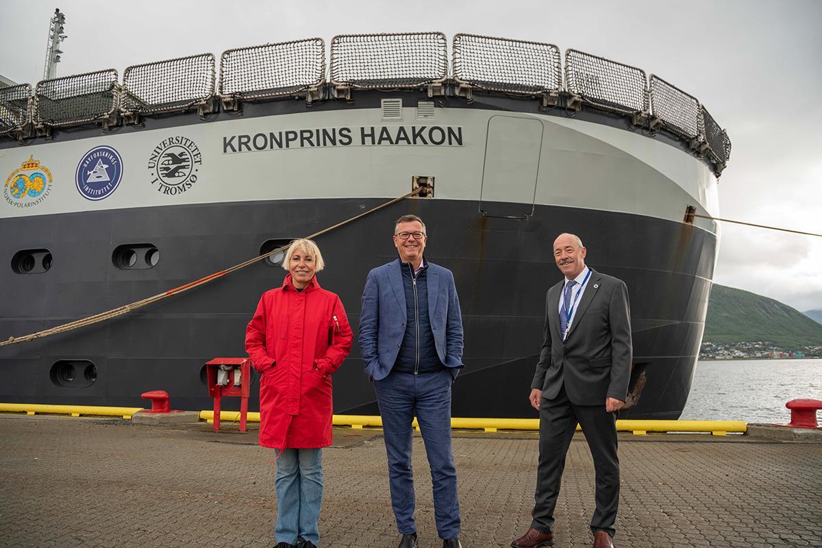 En kvinne og to menn foran baugen på forskningsskipet Kronprins Haakon ved kai i Tromsø