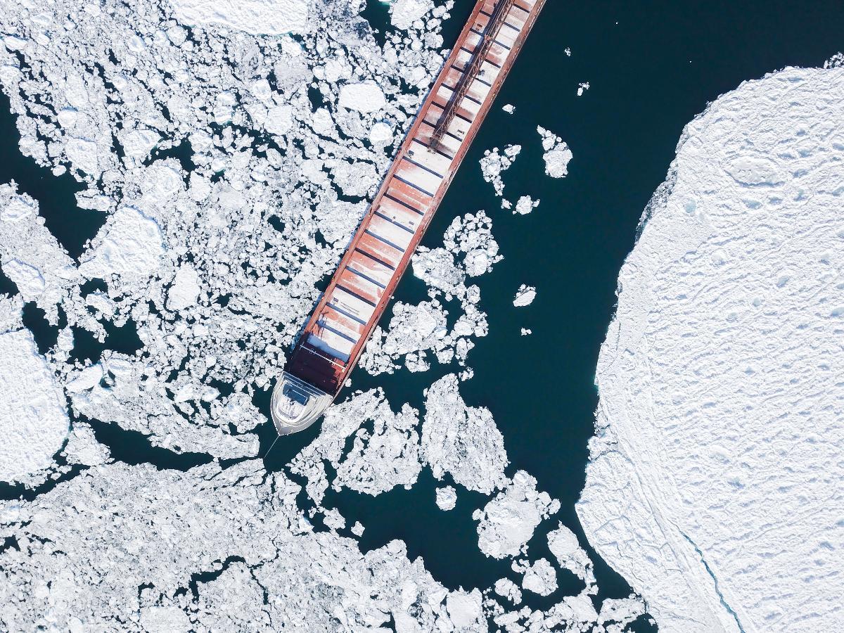 Dronefoto av et langt skip i havisen