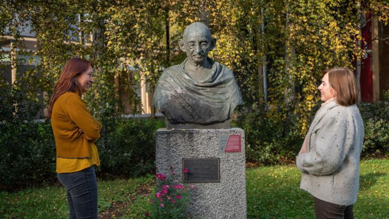 Marcela Douglas og Camilla Brekke ved Gandhi-statuen på campus i Tromsø. Foto: Christian Halvorsen / UiT