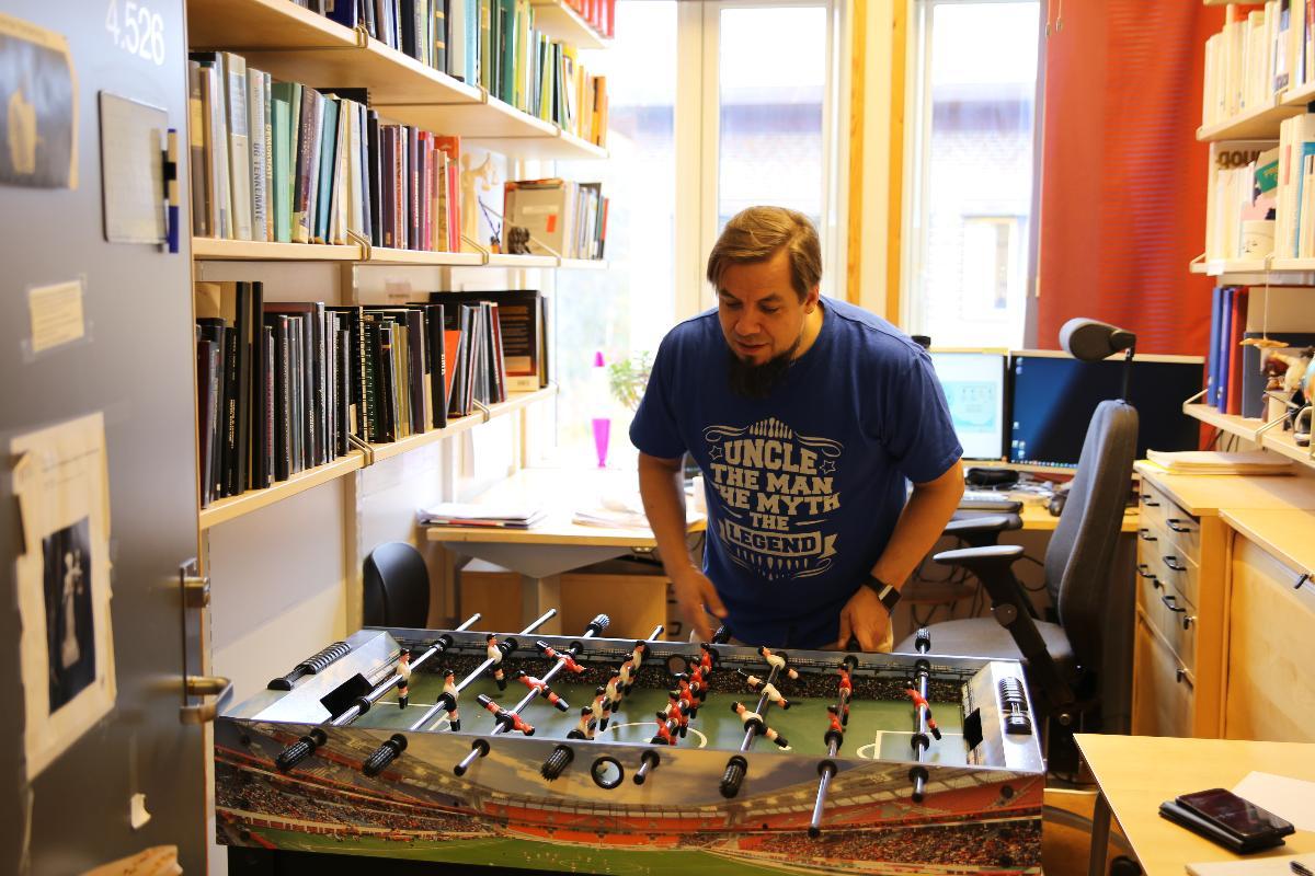 Marius Storvik viser frem foosballbordet han har på kontoret sitt, det har ingen tilknytning til utstillingen hans på Tromsø Museum.