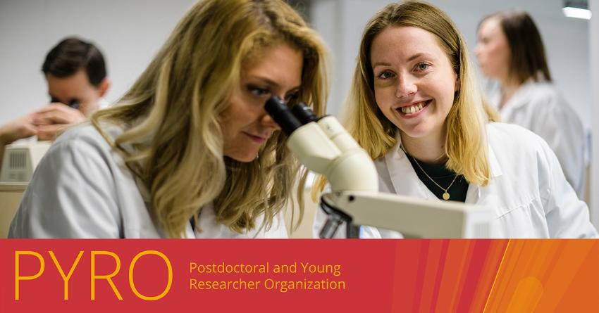 Smilende jente som sitter inne på et laboratorium med laboratoriefrakk på.