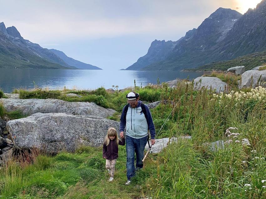 pappa som holder datter i hånda ute i naturen med en fiskestang i handa