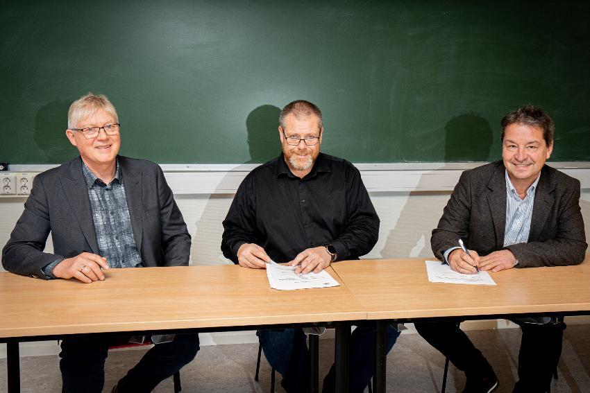 Bildet av tre representanter som signerer avtale.